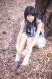 Una muchacha tailandesa asiática linda se está sentando con sus rodillas para arriba debajo del tr Fotografía de archivo libre de regalías