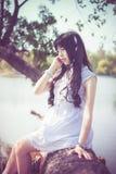 Una muchacha tailandesa asiática linda se está sentando en tronco de árbol de la orilla Fotografía de archivo libre de regalías