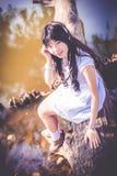 Una muchacha tailandesa asiática linda se está sentando en un tronco de árbol de la orilla Foto de archivo libre de regalías