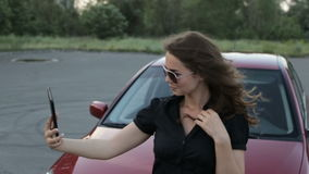 Una muchacha toma una fotografía de sí misma con una tableta en un fondo rojo del coche almacen de video