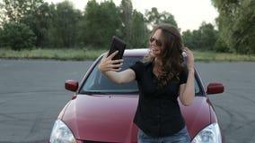 Una muchacha toma una fotografía de sí misma con una tableta en un fondo rojo del coche metrajes