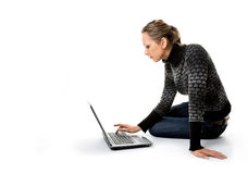 Una muchacha trabaja con el ordenador portátil que se sienta en el piso Foto de archivo libre de regalías