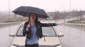 Una muchacha trastornada con un paraguas coge una situaci?n del coche en el camino bajo la lluvia almacen de video