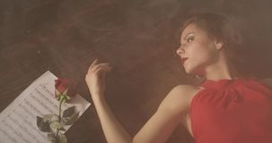 Una muchacha triste con los labios rojos miente en el piso oscuro en humo metrajes