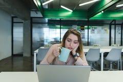 Una muchacha triste con una taza de café en sus manos utiliza un ordenador portátil en el escritorio en la oficina fotos de archivo