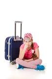 Una muchacha triste que se sienta con un bolso del viaje Fotos de archivo