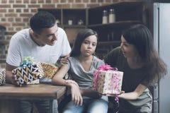 Una muchacha triste se sienta en una silla, y un hombre y una mujer alegres la mastican con los regalos para ella Imagenes de archivo