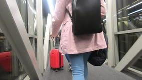 Una muchacha turística con una mochila detrás de ella pasa con la corrida en el aeropuerto, en sus manos ella celebra boletos y almacen de metraje de vídeo
