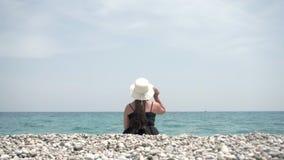 Una muchacha turística en un sombrero con los bordes anchos se sienta en la orilla del mar caliente y admira la hermosa vista del almacen de metraje de vídeo