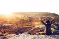 Una muchacha turística en un sombrero se sienta en una montaña y mira la salida del sol y los globos en Cappadocia Turismo, hacie Foto de archivo libre de regalías