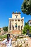 Una muchacha turística está tomando una foto del templo de Antoninus y de Faustina en Roman Forum imagenes de archivo