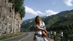 Una muchacha turística rubia joven en una falda está caminando abajo del camino en las montañas y está mirando el teléfono metrajes