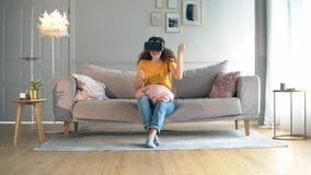 Una muchacha utiliza los vidrios de VR, sentándose en un sofá Robot, cyborg y concepto humano metrajes