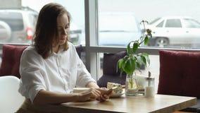 Una muchacha utiliza un teléfono celular que se sienta en un café una mujer joven envía un mensaje con el teléfono móvil y el caf Imágenes de archivo libres de regalías