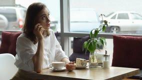 Una muchacha utiliza un teléfono celular que se sienta en un café una mujer joven envía un mensaje con el teléfono móvil y el caf Foto de archivo libre de regalías