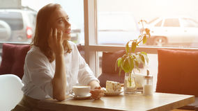 Una muchacha utiliza un teléfono celular que se sienta en un café una mujer joven envía un mensaje con el teléfono móvil y el caf Fotos de archivo libres de regalías