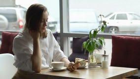 Una muchacha utiliza un teléfono celular que se sienta en un café una mujer joven envía un mensaje con el teléfono móvil y el caf Fotos de archivo