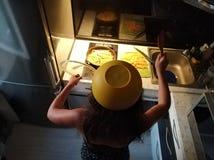 Una muchacha valiente del corazón en armadura de la materia de cocina que la protege contra el aceite caliente patata de la frita fotos de archivo libres de regalías