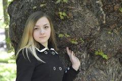 Una muchacha y un árbol viejo grande Foto de archivo