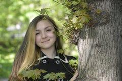 Una muchacha y un árbol viejo grande Fotografía de archivo