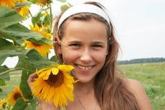 Una muchacha y un girasol Imagenes de archivo