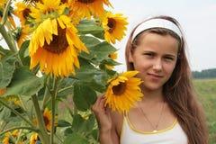 Una muchacha y un girasol Imagen de archivo