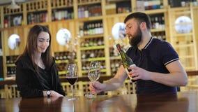 Una muchacha y un individuo en un restaurante comunican y beben el vino rojo, un vino rojo de las bebidas jovenes de los pares en almacen de video