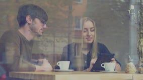 Una muchacha y un individuo en un café almacen de metraje de vídeo