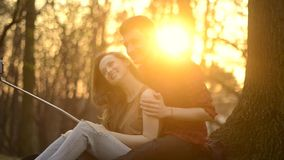Una muchacha y un individuo están descansando en el parque, besándose, abrazo, riendo en el Sunse metrajes