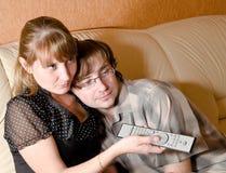 Una muchacha y un muchacho con la TV teledirigida Imagenes de archivo