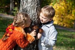 Una muchacha y un muchacho están jugando escondite Imágenes de archivo libres de regalías