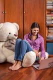 Una muchacha y un oso con un ordenador portátil Imágenes de archivo libres de regalías