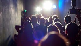 Una muchedumbre de gente con la iluminación es un pasillo estrecho metrajes
