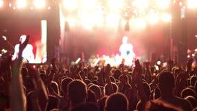 Una muchedumbre de gente en un concierto, una demostración de las manos que agitan, músicos de la roca de la palmada en la etapa  metrajes