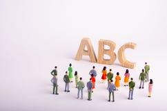 Una muchedumbre de gente es permanente y de mirada de las letras del alfabeto ABC Educación, guarderías y escuelas disponibles, Foto de archivo libre de regalías