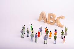 Una muchedumbre de gente es permanente y de mirada de las letras del alfabeto ABC Educación, guarderías y escuelas disponibles, c Imagen de archivo libre de regalías