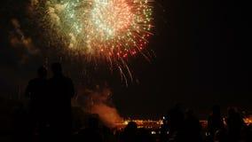Una muchedumbre de gente mira los fuegos artificiales coloridos y celebra metrajes