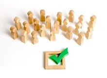 Una muchedumbre de miradas de la gente en una marca de verificación verde Concepto de la votación y de la elección Referéndum, re imagen de archivo