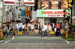 Una muchedumbre de peatones japoneses espera en una travesía de ferrocarril debajo de muestras coloridas Imagenes de archivo
