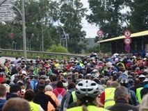 Una muchedumbre grande de jinetes de la bicicleta que esperan en un camino público Imagen de archivo libre de regalías