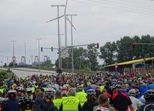 Una muchedumbre grande de jinetes de la bicicleta que esperan en un camino público Fotos de archivo libres de regalías