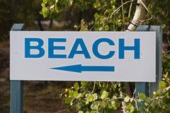 Una muestra azul de la playa con una flecha de la dirección Fotografía de archivo