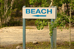Una muestra azul de la playa con una flecha de la dirección Imagen de archivo libre de regalías