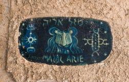 Una muestra con el nombre de la calle en hebreo - carril de la muestra del zodiaco Leo adentro en la ciudad vieja Yafo en el telé foto de archivo