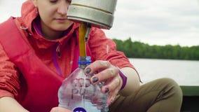 Una muestra de colada del científico de agua del lago en la botella plástica almacen de metraje de vídeo