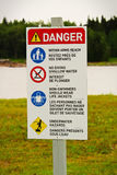 Una muestra del peligro de la playa con reglas en inglés y francés Imagen de archivo