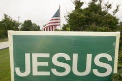 Una muestra lee a Jesús que promueve el punto de vista cristiano junto a una bandera americana, representando la separación de ig Fotografía de archivo