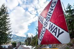 Una muestra roja del cruce ferroviario con las pistas de ferrocarril y una montaña en el fondo fotos de archivo