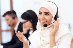Una mujer árabe trabaja en un centro de atención telefónica El árabe trabaja en la oficina fotos de archivo