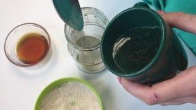 Una mujer añade la miel líquida a la harina Para la preparación de la levadura para el pan que cuece en casa Otros ingredientes s almacen de video